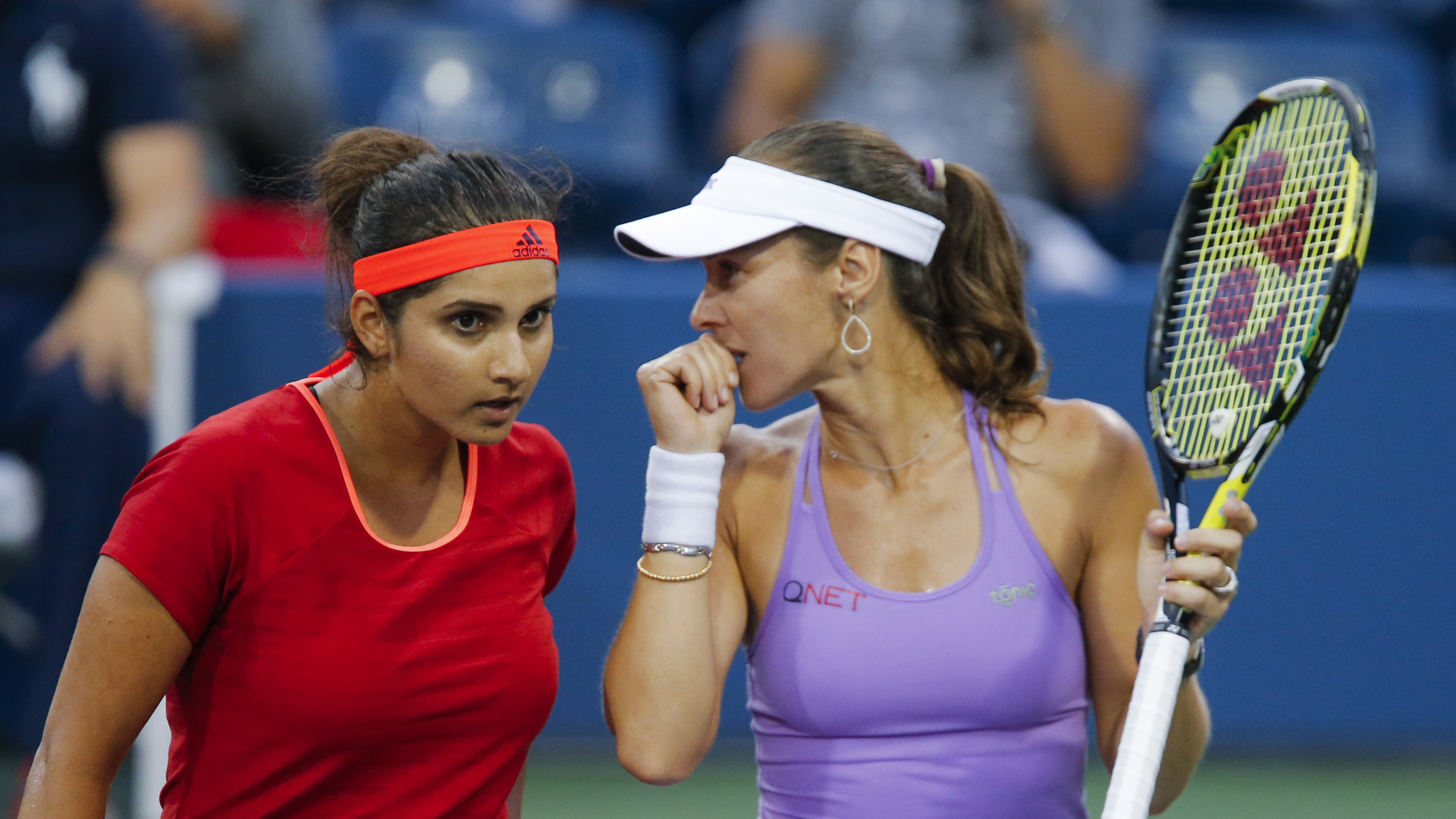 Sania Mirza of India (L) confers with playing partner Martina Hingis of Switzerland during their women's doubles semifinals match against Sara Errani and Flavia Pennetta, both of Italy, at the U.S. Open Championships tennis tournament in New York, September 9, 2015. REUTERS/Eduardo Munoz - RTSED6