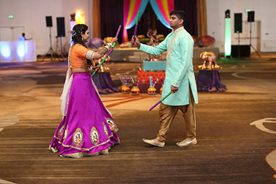 Indian Bride and Groom Playing Dandiya Raas