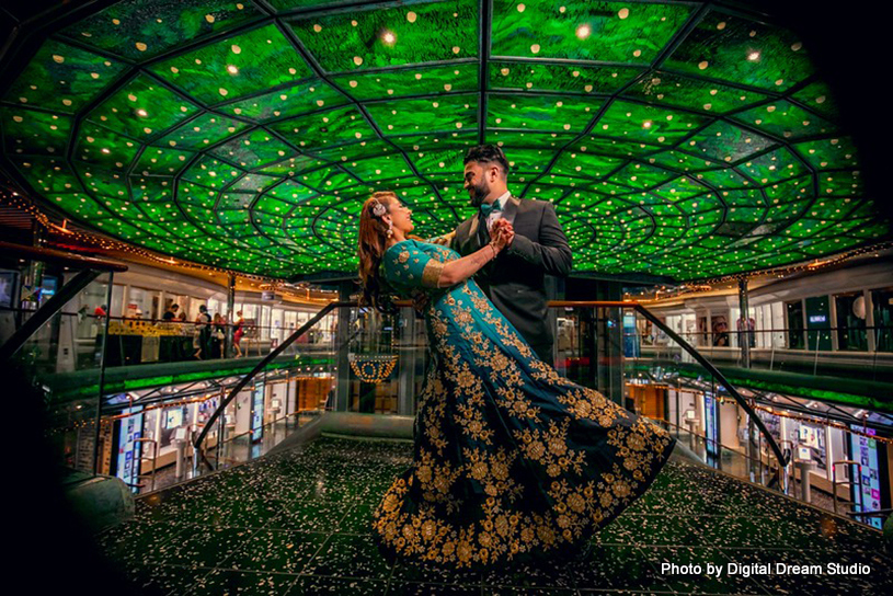 Indian bride and groom posing under incredible venue decor