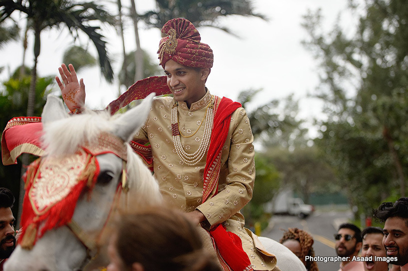 Indian groom riding on a horse at the baraat