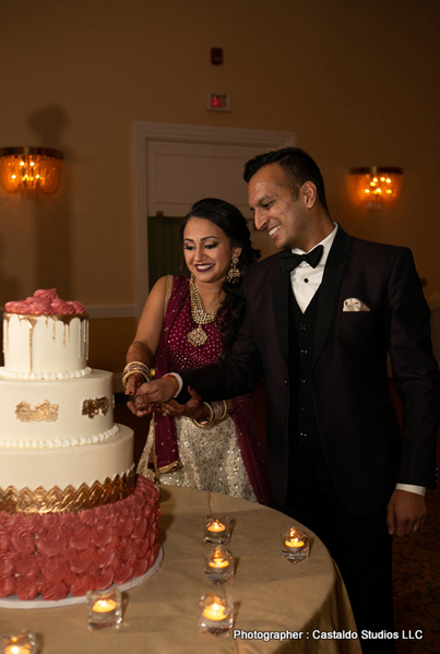 Cheerful Indian bride and groom cutting the cake.