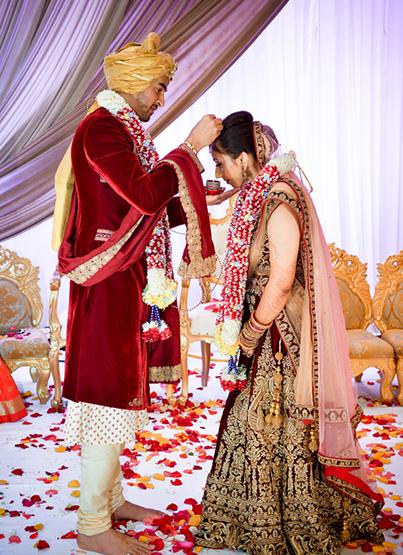 Groom applying sindoor to the bride