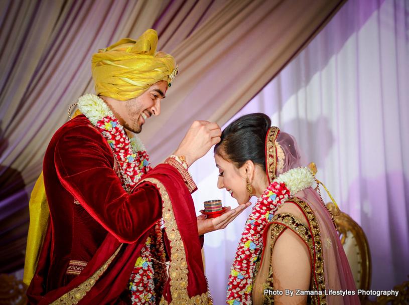 Indian Groom applying Sindoor to Bride