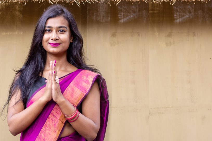 Young pretty asian or Indian woman doing namaste and greeting at