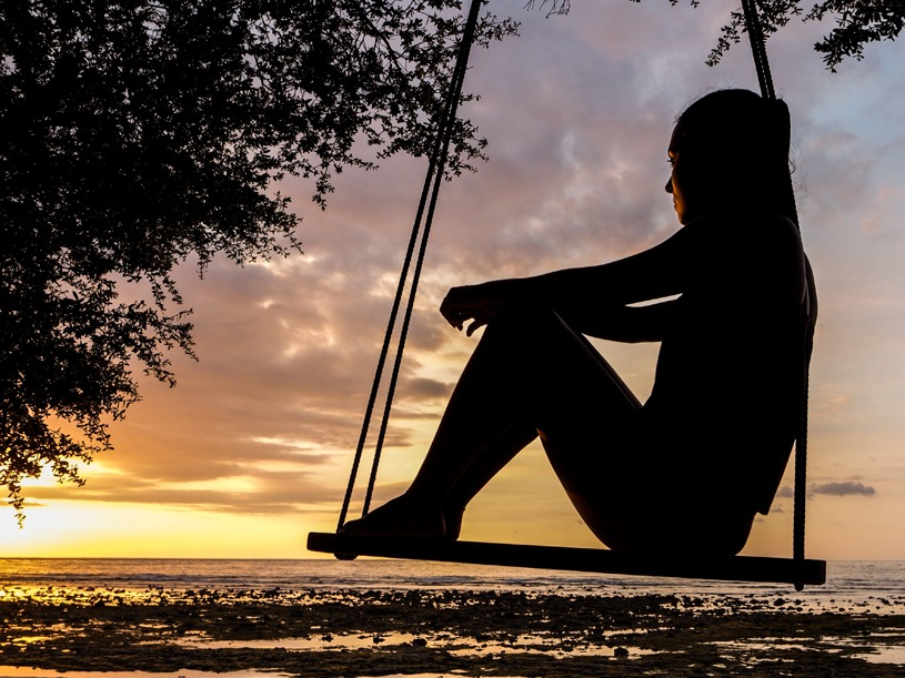 Girl Sitting alone on a swing