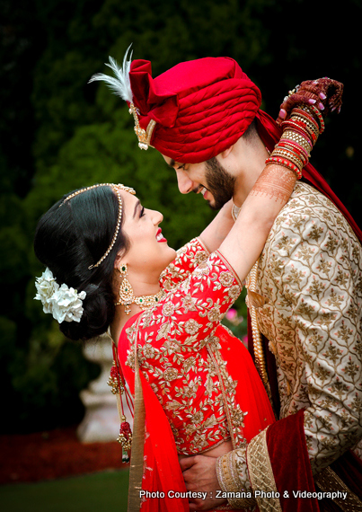 Indian bride and groom posing with their sangeet outfits