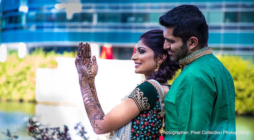 Beautiful indian bride showing henna art to groom