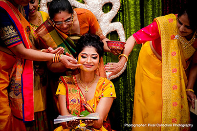 Indian wedding ritual of painting the bride with yellow turmeric paste