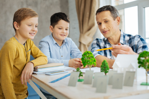 Young engineer discussing his eco-city project with sons