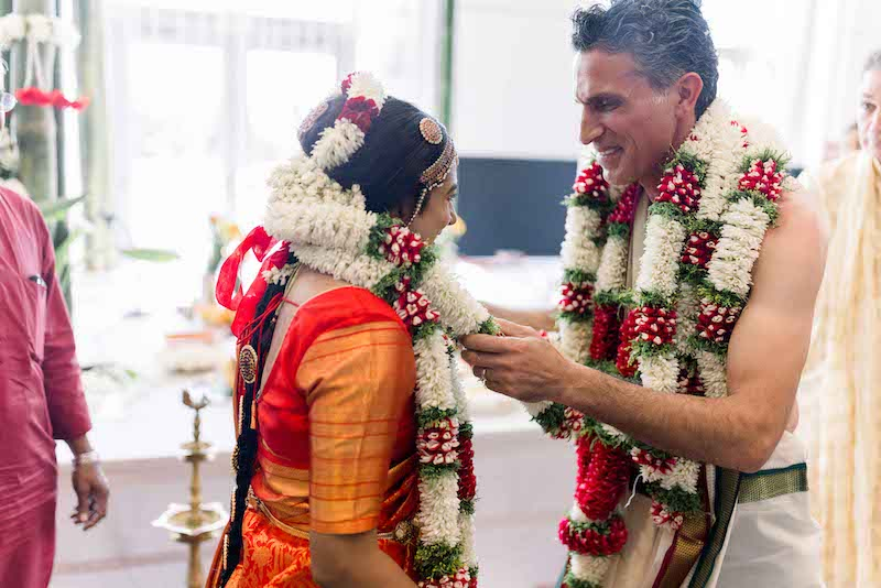Indian groom wears garland to bride
