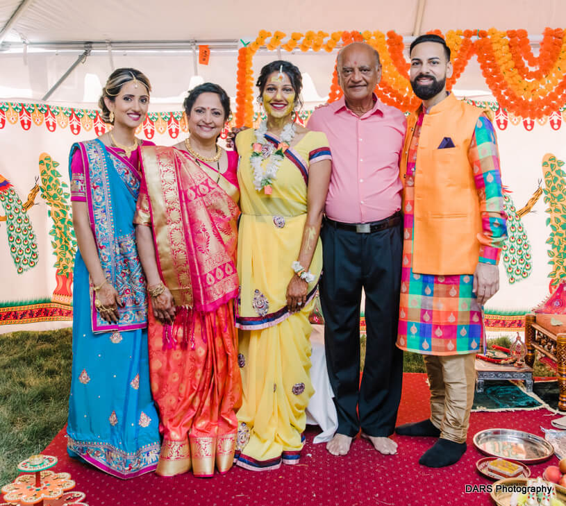 Bride Posing With Family Members at Haldi Ceremony