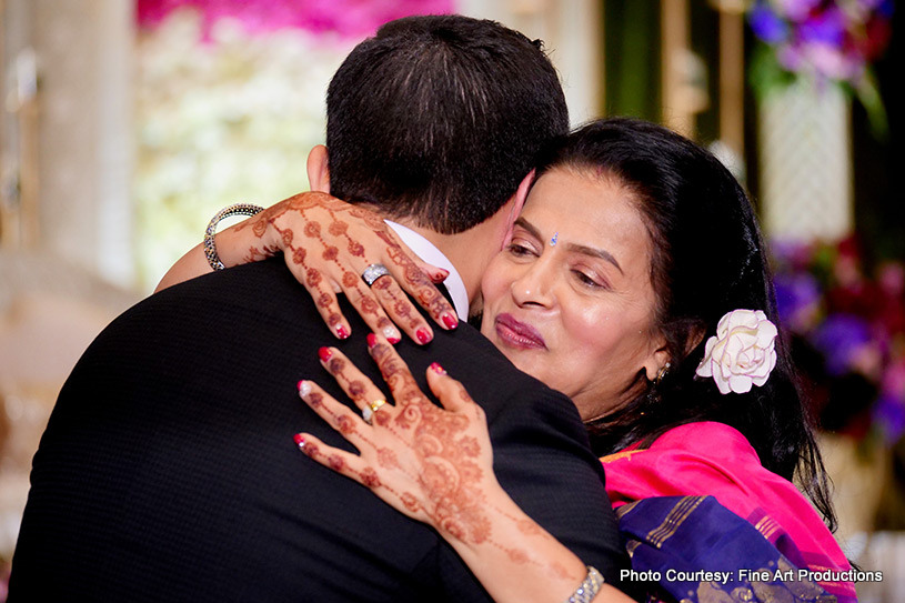 Indian groom giving a hug to his mother