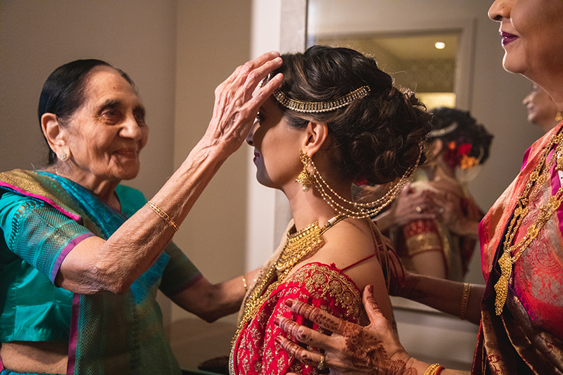 Indian Bride's Grand Mother helping bride to get ready