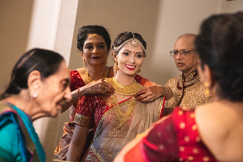 Parents helping bride getting ready for her wedding