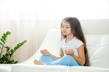 Happy kid girl doing yoga at home