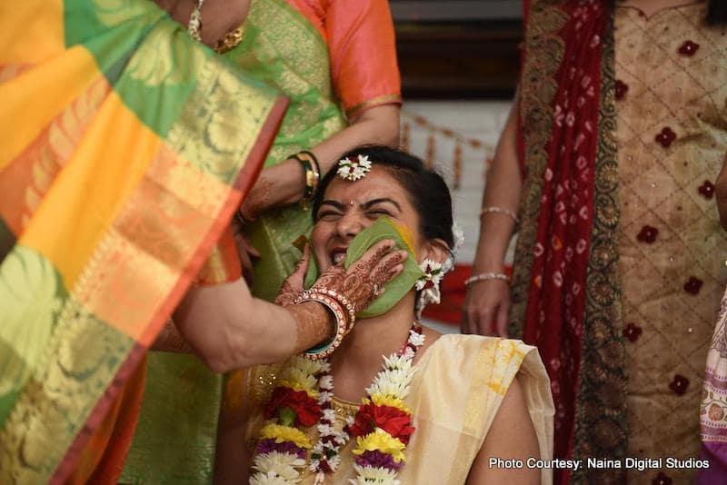 Indian bride mother applying haldi on bride's face
