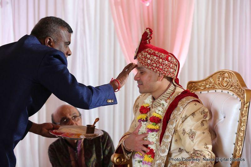 Indian Groom's fathet putting tika on Indian Groom's Head