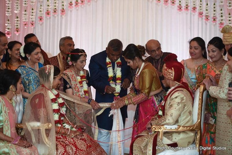 Indian couple doing ritual wih their family