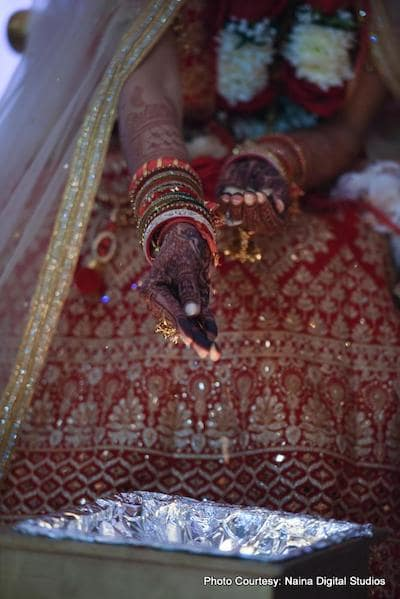 Indian bride putting something in holy fire